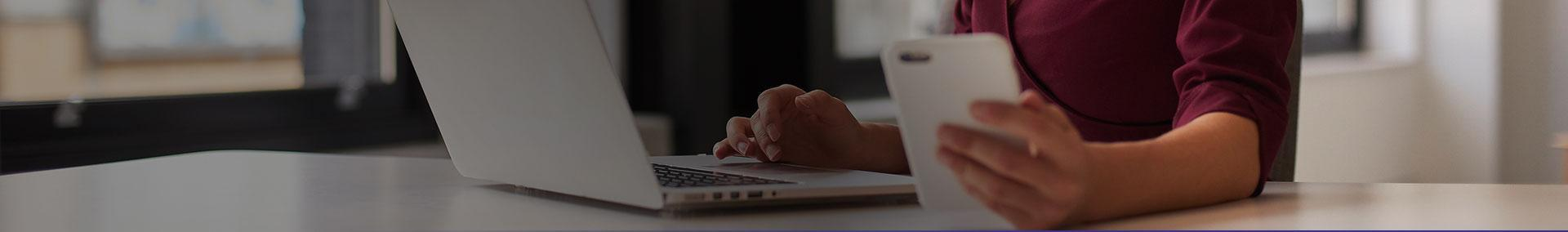 Smartphone w ręce i laptop